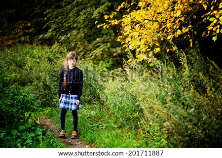 School girl in navy blue uniform has fun in the autumn forest after school