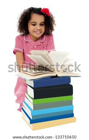 School girl in uniform sitting behind pile of books and preparing for examination. - stock photo