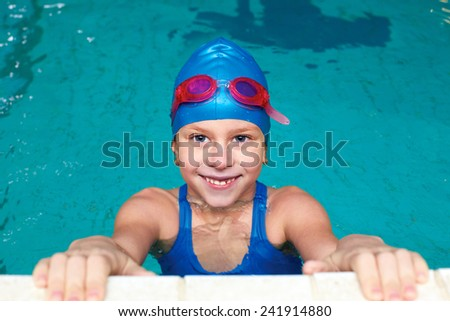 school girl is preparing start to swim on her back in the pool - stock photo