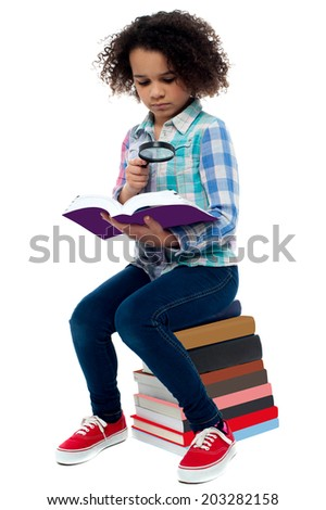 School girl sitting on the heap of books and reading - stock photo