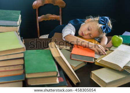 School girl sleeping at the table with many books and one green apple. Many homeworks or exam - is stress for little kids. Motivate your child to study a boring subject. Student. Pupil studying - stock photo