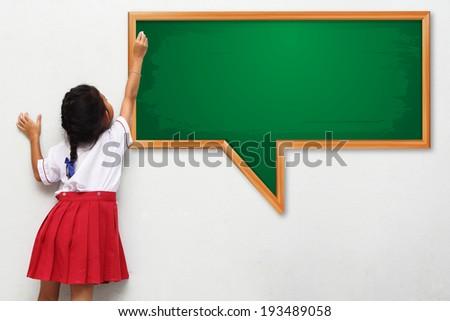 School girl standing in class near a green blackboard - stock photo