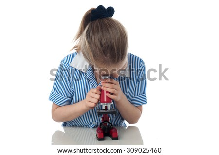 School girl working with a microscope at lap