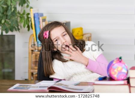 School girl yawns over books and homework - stock photo