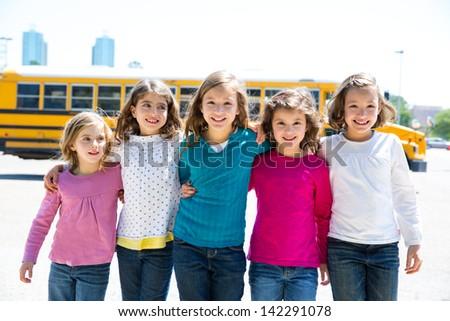 school girls friends sisters in a row walking from yellow school bus lot - stock photo