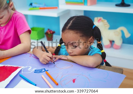 School girls painting a picture at their desk - stock photo