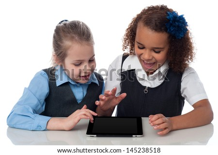 School girls playing on touch pad - stock photo