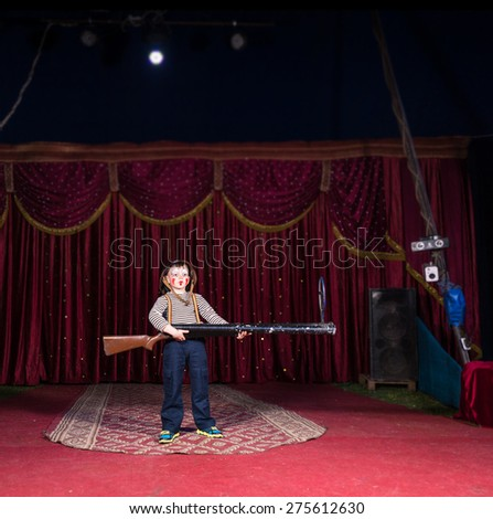 School history scene with a boy acting as a soldier ready to shoot the enemy with a big riffle - stock photo