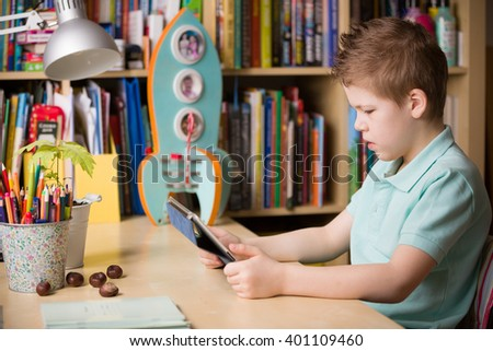 School kid boy sitting at his table and watching tablet pc at home, indoors. Child with tablet computer in his room. Studying with tablet computer. - stock photo