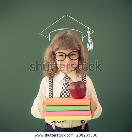 School kid in class. Happy child against green blackboard. Education concept - stock photo