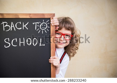 School kid in class. Happy child holding blackboard blank. Education concept - stock photo