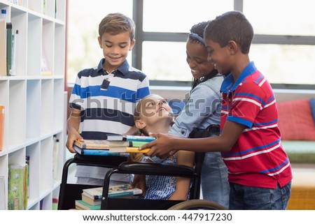 School kids giving books to disabled girl in library at school - stock photo