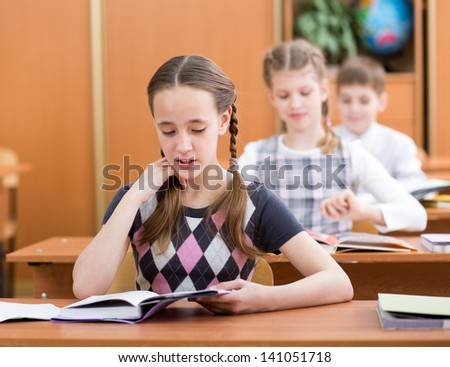 School kids in classroom. Girl reading task aloud at lesson.