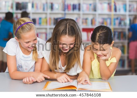School kids reading book together in library at elementary school - stock photo