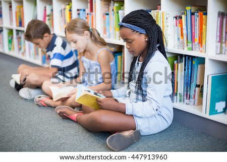 School kids sitting on floor and reading book in library at school - stock photo