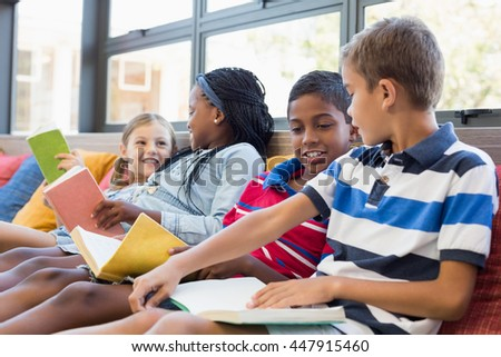 School kids sitting on sofa and reading book in library at school - stock photo