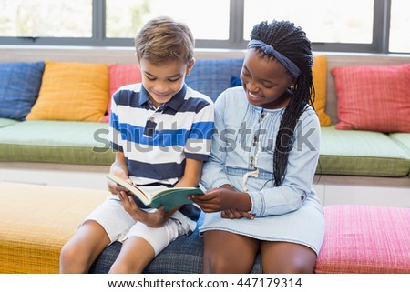 School kids sitting together on sofa and reading book in library