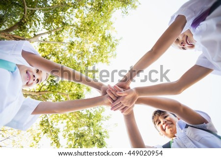 School kids stacking hands in campus at school - stock photo