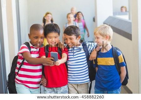 School kids taking selfie on mobile phone in corridor at school