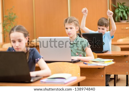 school kids using laptop at lesson in classroom - stock photo