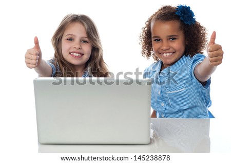 School kids with laptop gesturing thumbs up - stock photo