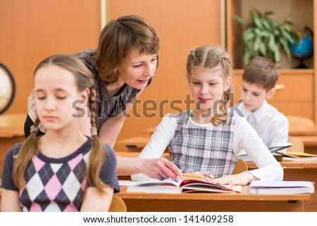 School kids work at lesson. Teacher controlling learning process. - stock photo