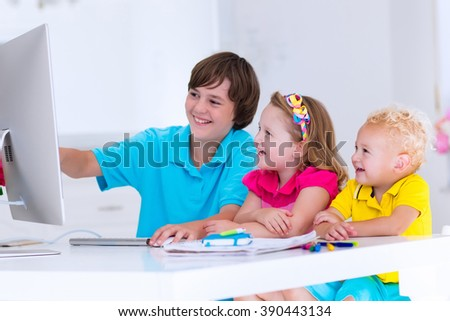School kids working on personal computer at home. Student doing homework using modern pc in classroom. Kids studying with digital devices. Children study in white class room. Child learning. - stock photo