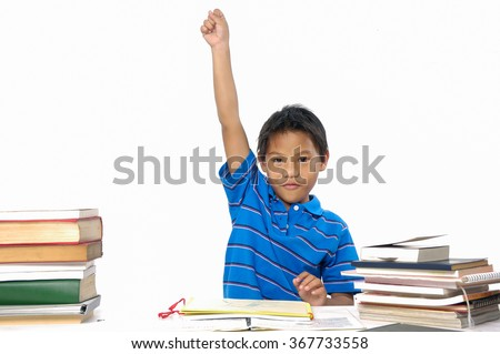 School little boy sitting and doing homework with hands up - stock photo
