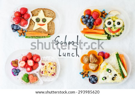 school lunch boxes for kids with food in the form of funny faces. the toning. selective focus - stock photo