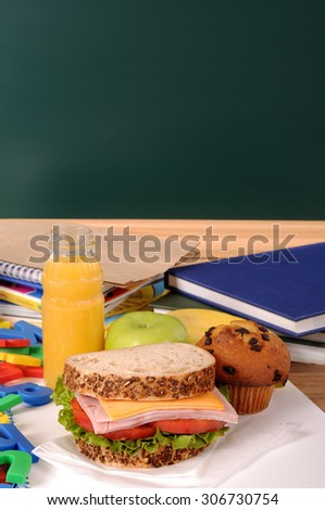School lunch on classroom desk with blackboard, copy space - stock photo