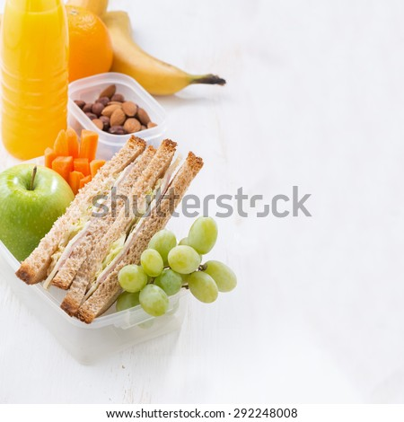 school lunch with sandwich on white wooden table, close-up - stock photo