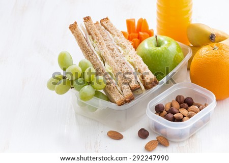 school lunch with sandwich on white wooden table, close-up, horizontal - stock photo