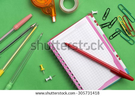 School materials such as crayons, notebooks, clips, stapler, prencils over green background - stock photo