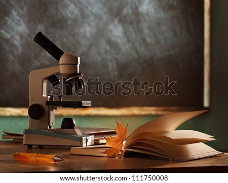School microscope in classroom on blackboard  background - stock photo