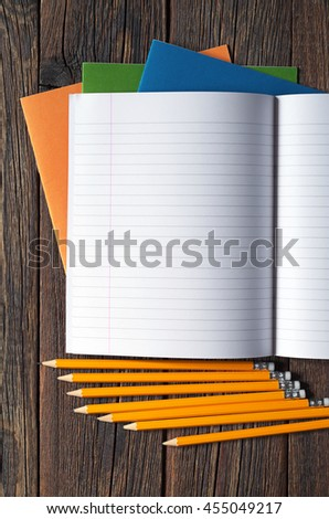 School notebooks and pencils on dark wooden table, top view