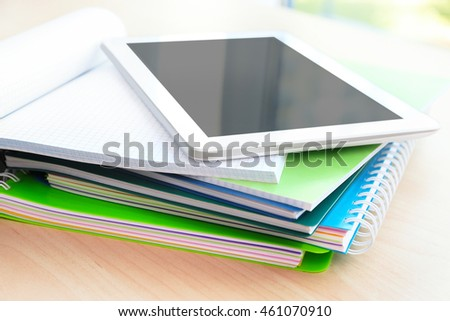 School notebooks and tablet, closeup