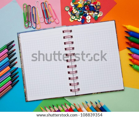 School, office, or artistic accessories - open notebook, colored paper, colored pencils, markers, paper clips, buttons. Ready for your logo, text or symbol.