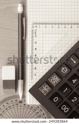 School or office supplies on a wood background toned in sepia - stock photo