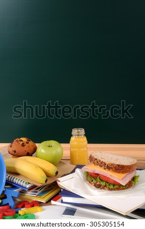 School packed lunch on student desk, blackboard, copy space, vertical - stock photo