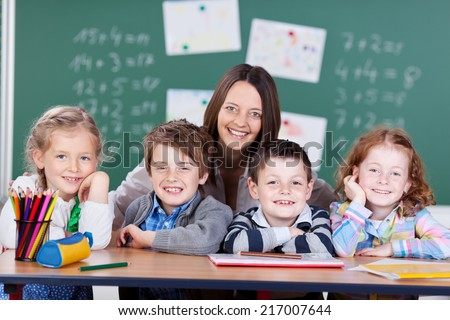 School portrait of an attractive friendly young female teacher with a group of her little students sitting in a row at a desk smiling at the camera, girls and boys - stock photo