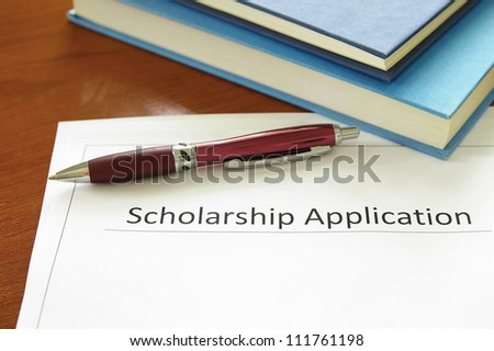 school scholarship application form and books - stock photo