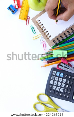 School stationery and human hand writing on small notebook on white background. Back to school concept - stock photo