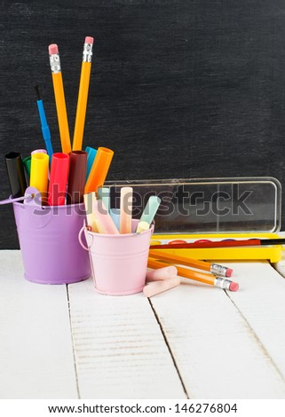 School stationery - pencils, markets, paints, chalk on white wooden background against empty blackboard. School/educational concept. Back to school. Selective focus. - stock photo