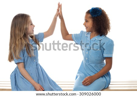School students giving high five in classroom - stock photo