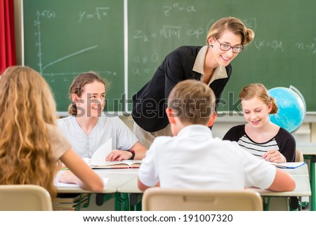 School Students or pupils having group work while geography lesson and the teacher test or educate them in class - stock photo