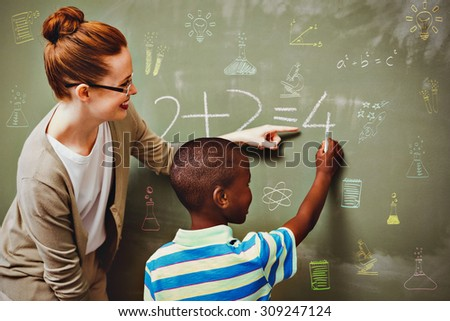 School subjects doodles against teacher assisting boy to write on blackboard in classroom - stock photo