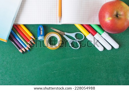 School supplies and apple on the chalkboard - stock photo