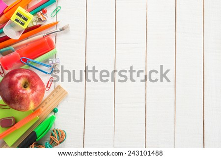 School supplies and apple on wooden background   - stock photo