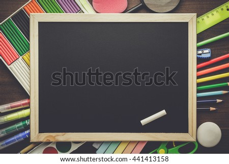 school supplies and blackboard with copy space on the table - stock photo