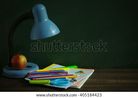 School supplies and blue desk lamp on a wooden surface against a blackboard. A desk lamp, notebooks, handles, colored pencils, rulers and red apple on a wooden table